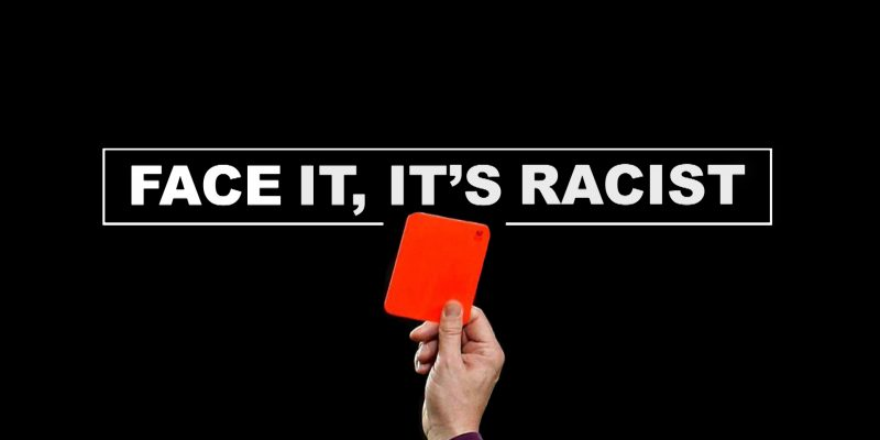 This is a photo of a referee showing a red card, with the words Face It, It's Racist in the background.