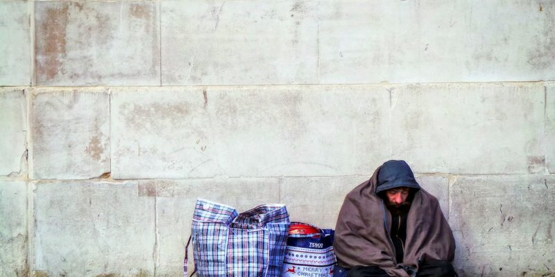 Photograph of homeless man and belongings on street