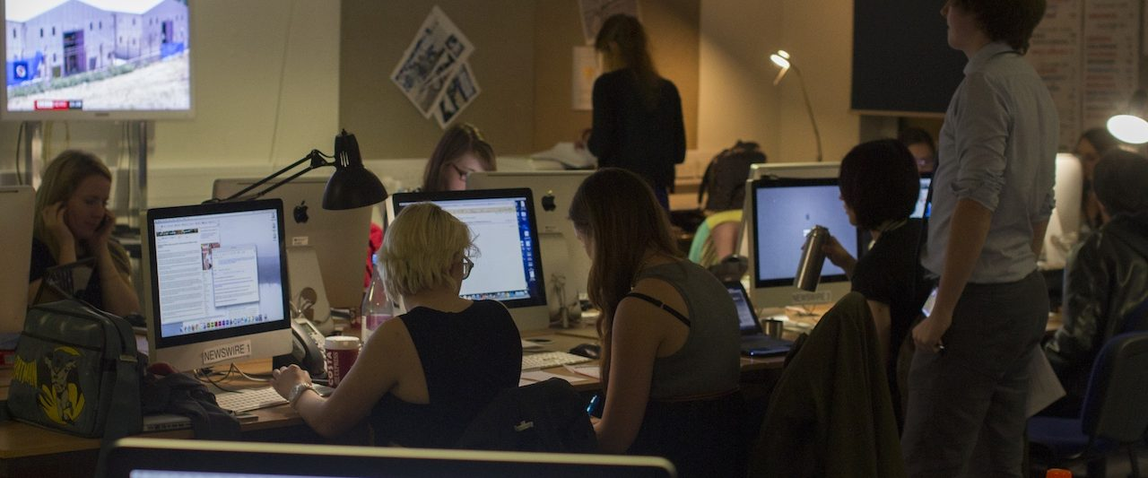 photograph of students working on the buzz website