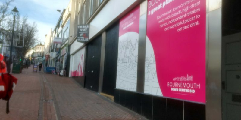 A poster saying 'Bournemouth - A great place to shop' next to a to let sign.