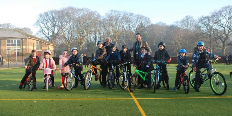 A photo of the school children on their bikes with Darryl Walsh the headteacher