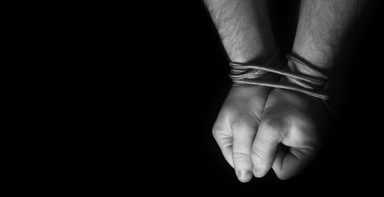 Hands tied with string.