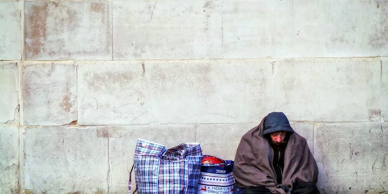 A homeless man sitting by a wall with few belongings