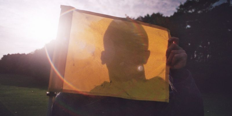 A picture of a person with a flag infront of their face, used to represent anonymity