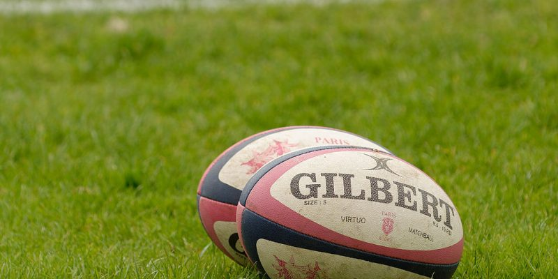 Photo of 2 rugby balls on a rugby pitch
