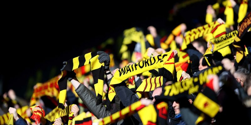Fans holding up Watford FC scarfs at football game (pre Covid-19)