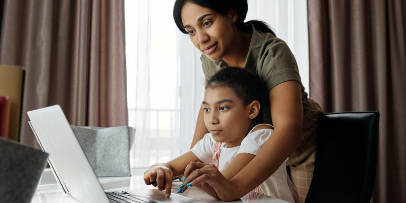 A mother and a child looking at a laptop screen together.