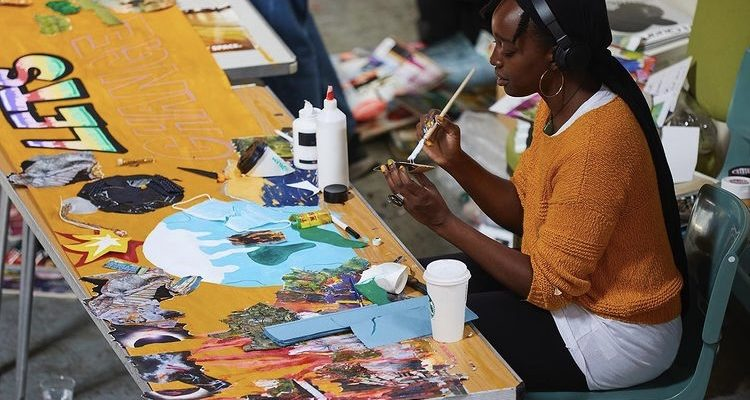 Image of young girl from homeless charity Accumulate, taking part in painting, a creative workshop.