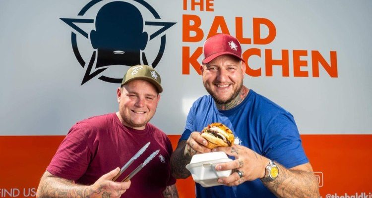 two men holding burgers