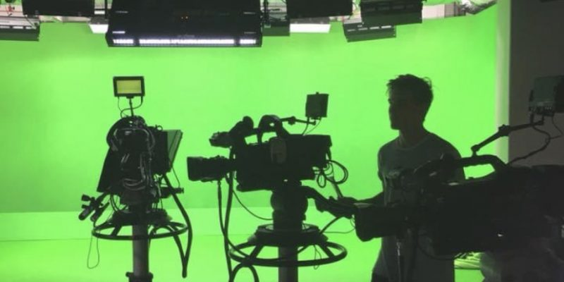 Harry stood with cameras in a green screen studio