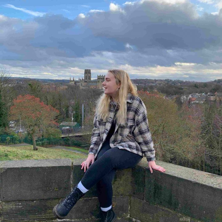 Jen sat on a wall with York landscape in the background