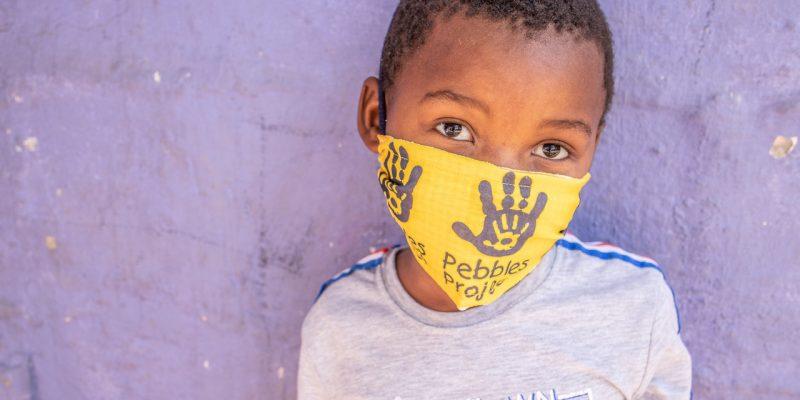 Child stood with bandana over face