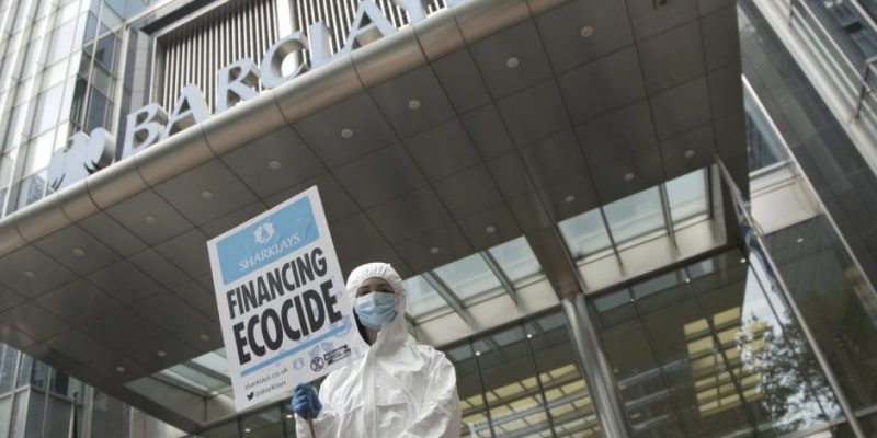 A man in a white suit and surgical mask holding a financial ecocide sign