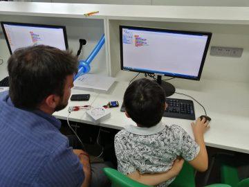 A student and a teacher sat at a computer