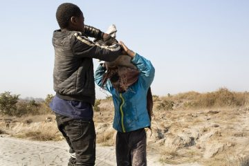A photo of two children struggling to carry a bag of cobalt.