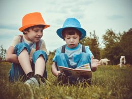 two boys sat on grass reading a book