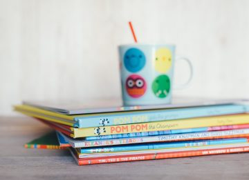 Stack of children's books with mug on top