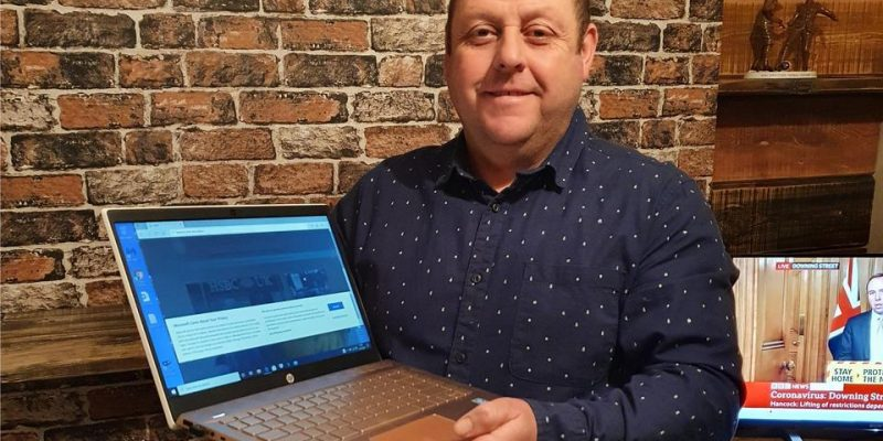 Sean Clayton, mayor of Ashbourne and founder of Laptops for Learners, holding a donated computer.