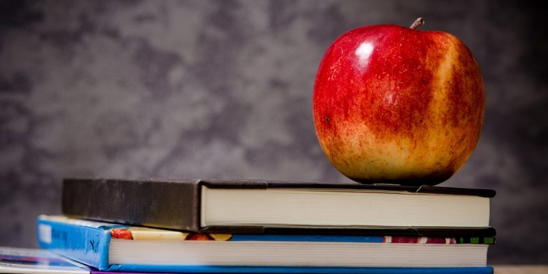 a picture of a red apple on top of some books