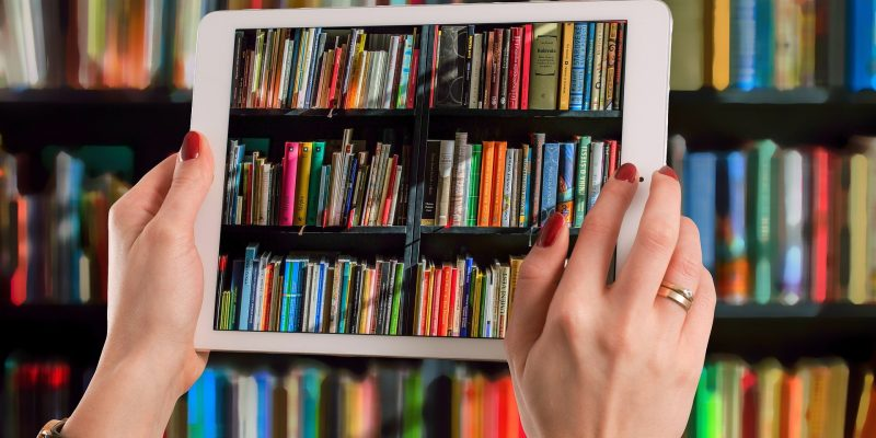 Image of a book shelf through a laptop